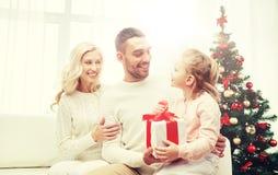 Lycklig familj hemma med julgåvan Royaltyfria Foton