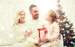 Lycklig familj hemma med julgåvan Royaltyfria Bilder