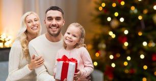 Lycklig familj hemma med julgåvan royaltyfri fotografi