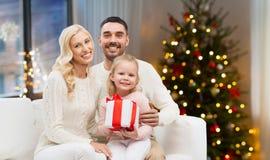 Lycklig familj hemma med julgåvan arkivfoto