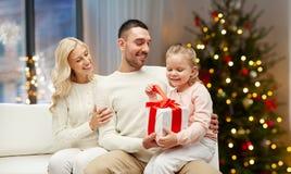 Lycklig familj hemma med julgåvan royaltyfri bild