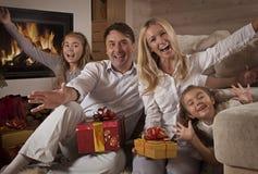 Lycklig familj hemma med julklappar Royaltyfri Fotografi