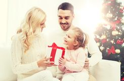 Lycklig familj hemma med julträdet Arkivfoto