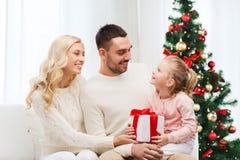 Lycklig familj hemma med julträdet Fotografering för Bildbyråer