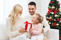 Lycklig familj hemma med julträdet Arkivbild