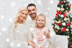 Lycklig familj hemma med julträdet Royaltyfria Foton
