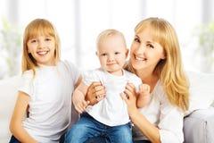 Lycklig familj hemma på soffan. Moder och dotter och son Arkivfoto