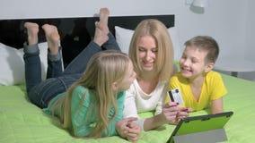 Lycklig familj hemma som använder en minnestavla till att shoppa direktanslutet lager videofilmer
