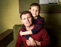 Lycklig familj. Hemmastadda fader och son. Arkivfoto