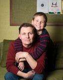 Lycklig familj. Hemmastadda fader och son. Arkivbilder