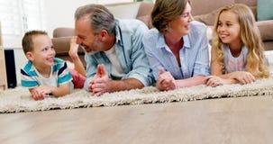Lycklig familj, i att ligga på filten i vardagsrum stock video