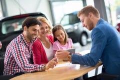 Lycklig familj i bilåterförsäljaren som väljer deras nya bil arkivbilder