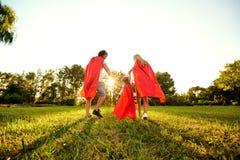 Lycklig familj i dräkter av superheroes i parkera på solnedgången royaltyfria bilder