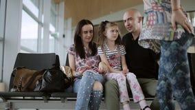 Lycklig familj i flygplatsvardagsrummet som väntar på ditt flyg arkivfilmer