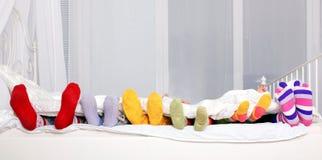 Lycklig familj i färgrika sockor på vit säng. Arkivfoton