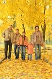 Lycklig familj i höstskog Arkivfoto