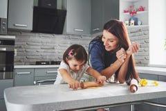 Lycklig familj i kök Feriematbegrepp Modern och dottern som förbereder degen, bakar kakor lycklig familj arkivbild