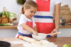 Lycklig familj i kök Moder- och barndottermatlagning semestrar pajen eller kakor för moderdag arkivbilder