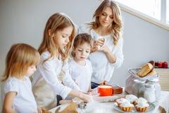 Lycklig familj i kök Modern och hennes gulliga ungar lagar mat kakor arkivbild