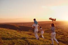 Lycklig familj i natur på solnedgången arkivbilder
