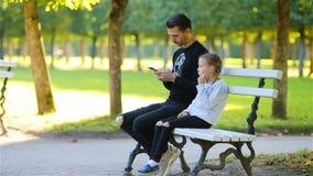 Lycklig familj i nedgång Fadern med smartphonen och den lilla ungen har gyckel på härlig höstdag lager videofilmer