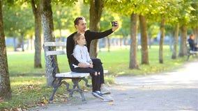 Lycklig familj i nedgång Fadern och den lilla ungen har gyckel som tar selfie på härlig höstdag lager videofilmer