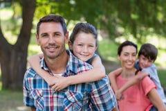 Lycklig familj i parkera tillsammans Arkivfoto