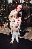 Lycklig familj i röda jultomtenhattar på julgranen arkivbild
