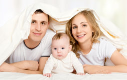 Lycklig familj i säng under en filt Arkivbild