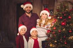 Lycklig familj i santa hattar Royaltyfria Bilder