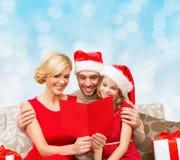Lycklig familj i santa hattar med hälsningkortet Fotografering för Bildbyråer