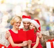 Lycklig familj i santa hattar med hälsningkortet Royaltyfri Foto