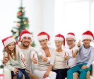 Lycklig familj i santa hattar som visar upp tummar Royaltyfria Foton