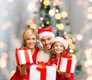Lycklig familj i santa hjälpredahattar med gåvaaskar Fotografering för Bildbyråer