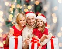 Lycklig familj i santa hjälpredahattar med gåvaaskar Arkivfoto