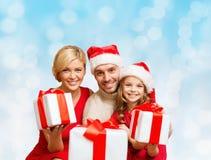 Lycklig familj i santa hjälpredahattar med gåvaaskar Arkivbilder
