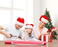 Lycklig familj i santa hjälpredahattar som packar gåvan Royaltyfria Foton
