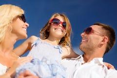Lycklig familj i solglasögon över blå himmel royaltyfri bild