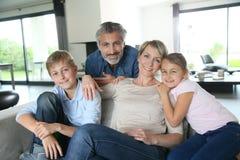 Lycklig familj i vardagsrumet royaltyfri foto