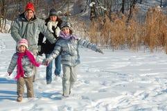 Lycklig familj i vinter och att ha gyckel med snö utomhus Royaltyfria Bilder