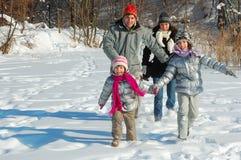 Lycklig familj i vinter och att ha gyckel med snö utomhus Fotografering för Bildbyråer