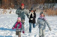 Lycklig familj i vinter och att ha gyckel med snö utomhus Arkivfoto