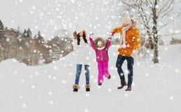 Lycklig familj i vinterkläder som utomhus går Arkivbilder