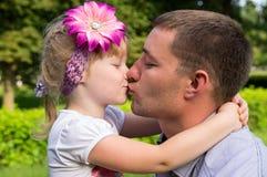 Lycklig familj, kyssande dotter för farsa royaltyfri fotografi