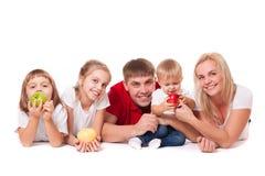 Lycklig familj med äpplen arkivfoto