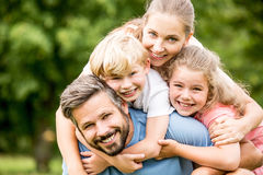 Lycklig familj med att krama för två ungar royaltyfri bild