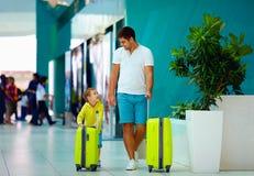 Lycklig familj med bagage som är klart för sommarsemester, i flygplats Arkivbild