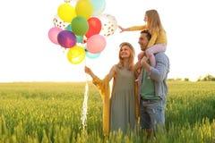 Lycklig familj med ballonger utomhus på solig dag royaltyfri fotografi