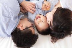 Lycklig familj med barn i säng Royaltyfri Fotografi
