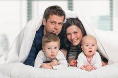 Lycklig familj med barn i säng arkivfoton